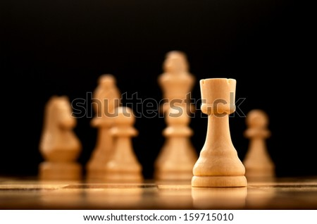 Low angle view of a single wooden chess piece, the pawn, on a chessboard with the rest of the pieces visible in the background, shallow dof - stock photo
