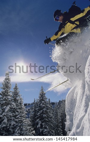 Low angle view of a skier jumping from snow bank through snow