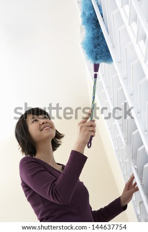 Low angle view of a smiling Asian woman dusting window