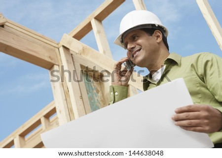 Low angle view of a smiling construction worker with cellphone and blueprints at site - stock photo