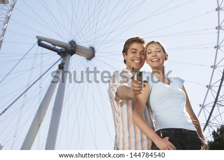 Low angle view of a vacationing couple photographing themselves with mobile phone against London Eye - stock photo