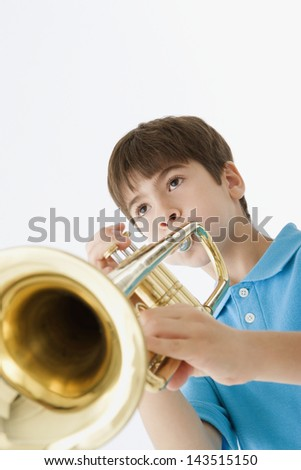 Low angle view of a young boy playing the trumpet - stock photo