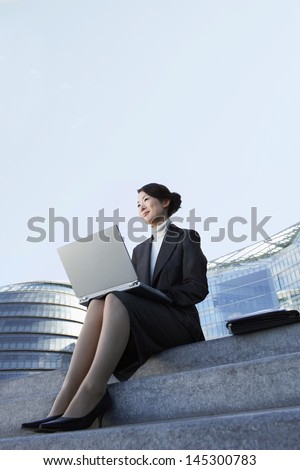 Low angle view of a young businesswoman using laptop on outdoor steps