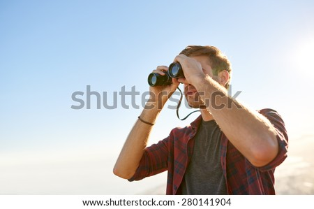 Low angle view of a young man looking through binoculars while outdoors in nature  - stock photo