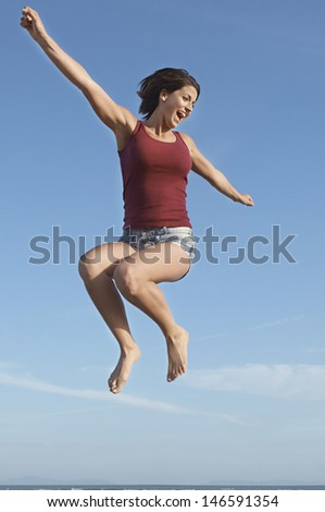 Low angle view of a young woman jumping in air against blue sky