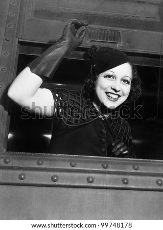 Low angle view of a young woman looking through the window of a train and smiling - stock photo
