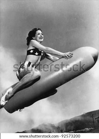 Low angle view of a young woman sitting on a rocket and smiling - stock photo
