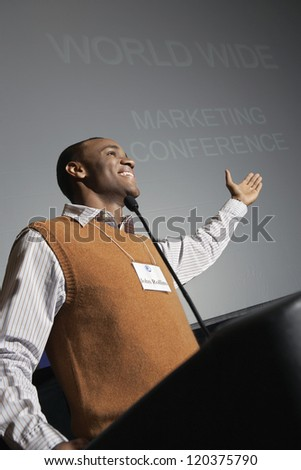 Low angle view of an African American businessman giving a speech on podium - stock photo