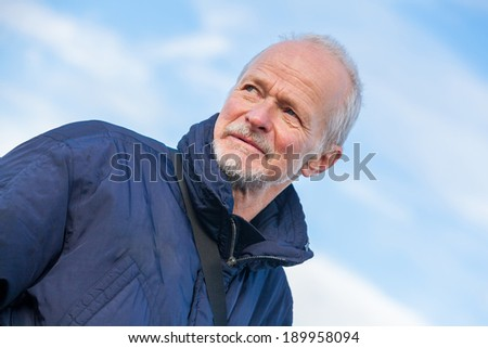 Low angle view of an attractive bearded senior man with a thoughtful expression staring off to the left of the frame - stock photo