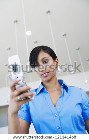 Low angle view of an Indian business woman reading text message on cell phone