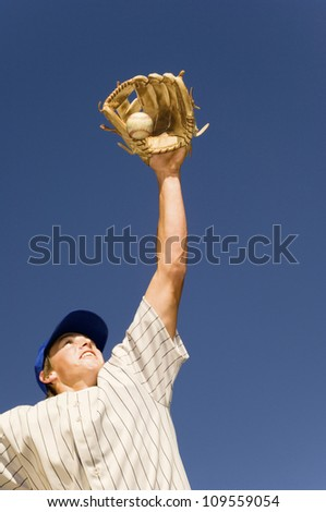 Low angle view of baseball player trying to catch the ball against blue sky - stock photo