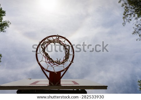 Low Angle View of Basketball Backboard, Basket, and Net Against Sunny Blue Sky with Clouds, Directly Underneath Basketball Hoop with Copy Space - stock photo