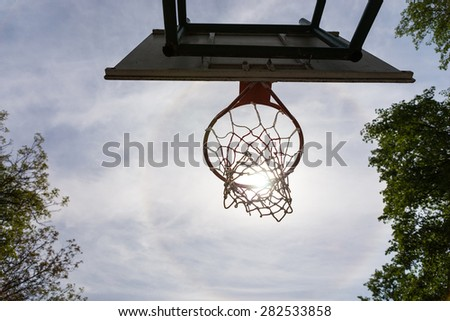 Low Angle View of Basketball Backboard, Hoop and Net Against Cloudy Blue Sky - Sun Framed by Basketball Basket as seen from Directly Underneath - stock photo