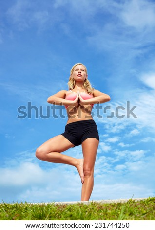 Low angle view of beautiful young woman practicing tree yoga pose against sky - stock photo