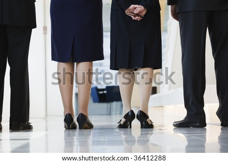 Low angle view of bottom half of businesspeople standing in a corridor waiting for a meeting.