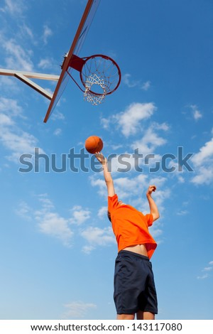 Low angle view of boy playing basketball against blue sky - stock photo