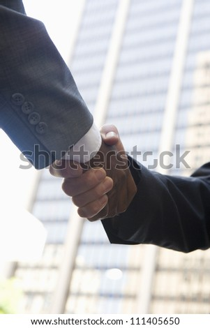 Low angle view of business people shaking hands - stock photo