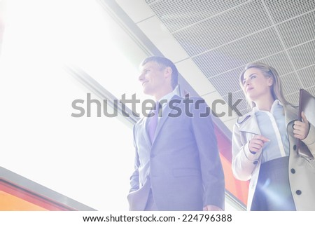 Low angle view of business people walking in railroad station - stock photo