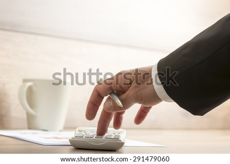Low angle view of businessman or accountant doing a calculation on a manual desk top calculator, close up of his hand holding a pen. - stock photo