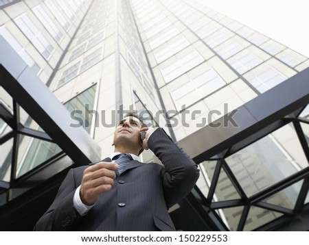 Low angle view of businessman using mobile phone against tall office building