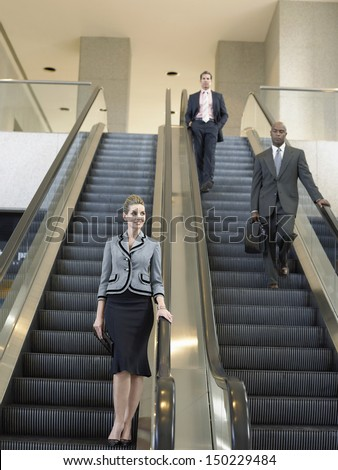 Low angle view of businesspeople moving down on escalator in office - stock photo