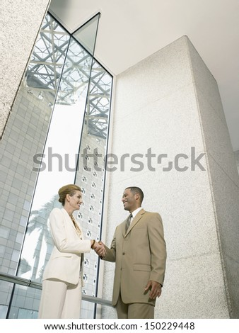 Low angle view of businesspeople shaking hands in office building - stock photo