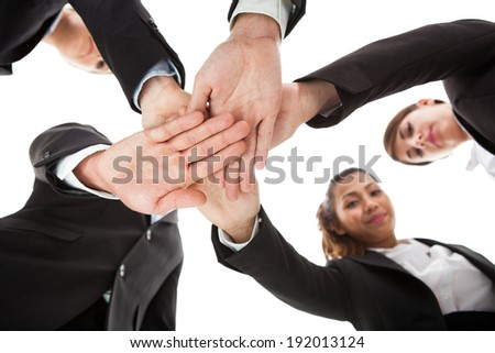 Low angle view of businesspeople stacking hands against white background