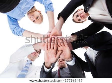 Low Angle View Of Businesspeople Stacking Hands Together Over White Background