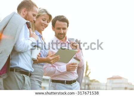 Low angle view of businesspeople using digital tablet against clear sky - stock photo