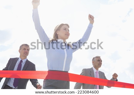Low angle view of businesswoman crossing finishing line with colleagues in background - stock photo