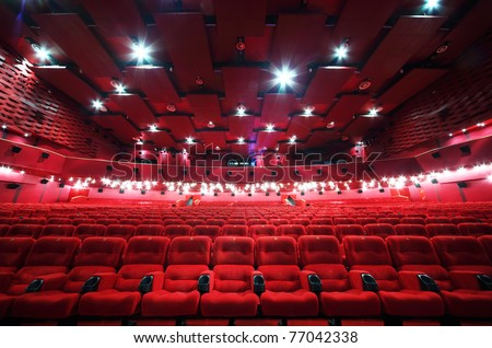 Low-angle view of ceiling and rows of comfortable red chairs in illuminate red room cinema - stock photo