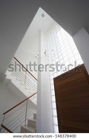 Low angle view of chandelier hanging near doorway and staircase in townhouse - stock photo