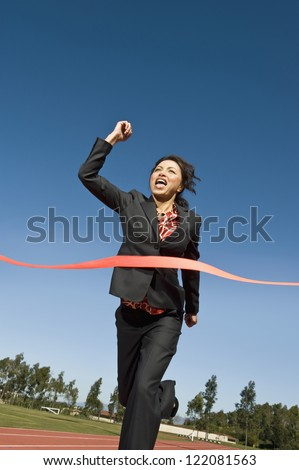 Low angle view of cheerful business woman crossing the finish line of racing track against blue sky