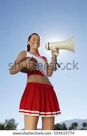 Low angle view of cheerleader holding megaphone and ball