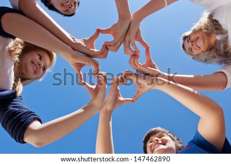 Low angle view of children and teacher forming hearts against clear blue sky - stock photo