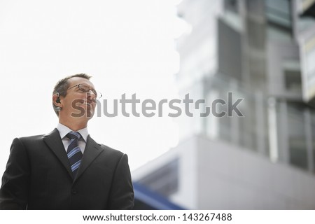 Low angle view of confident businessman wearing wireless headset against sky - stock photo