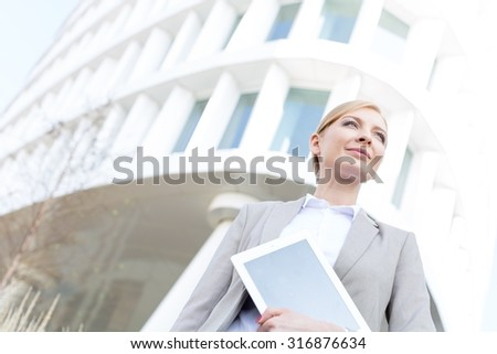 Low angle view of confident businesswoman holding digital tablet outside office building - stock photo