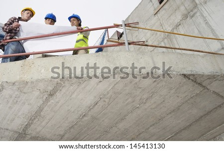 Low angle view of construction team examining building plans at site - stock photo
