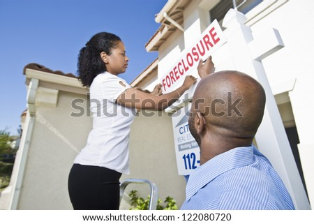 Low angle view of couple putting notice outside the house - stock photo