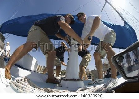 Low angle view of crew members operating windlass on yacht - stock photo
