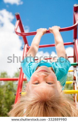 Low angle view of cute blond girl wearing blue teeshirt hanging from a monkey bars. Girl is hanging upside down looking at camera smiling. The climbing frame is located in the courtyard of a house - stock photo