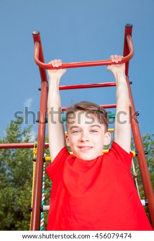 Low angle view of cute teen boy wearing red tshirt hanging  from a climbing frame in a playground looking at camera smiling