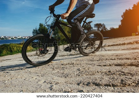 low angle view of cyclist riding mountain bike on rocky trail