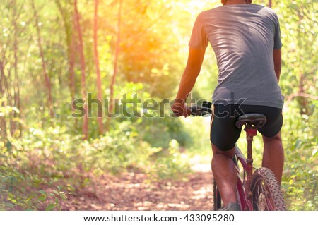 low angle view of cyclist riding mountain bike on rocky trail at - stock photo