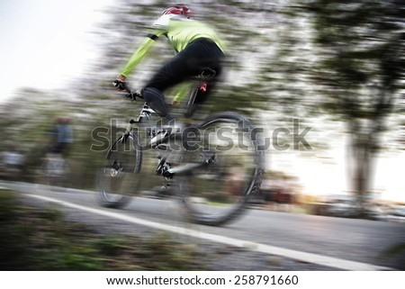 Low angle view of cyclist riding mountain bike with speed effect - stock photo