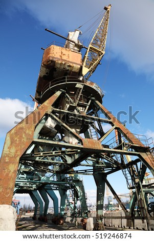 Low angle view of dock crane in the port in front of blue sky with white clouds