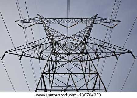 Low angle view of extremely tall electrical tower and power lines - stock photo