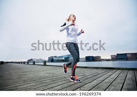 Low angle view of female athlete running along waterfront. Young woman jogging on boardwalk by the river. - stock photo