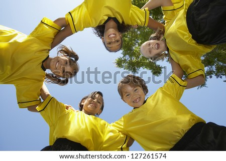 Low angle view of female football team forming huddle against clear sky - stock photo