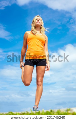 Low angle view of fit young woman stretching at beach - stock photo